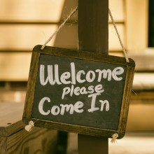Welcome please come in written on a blackboard